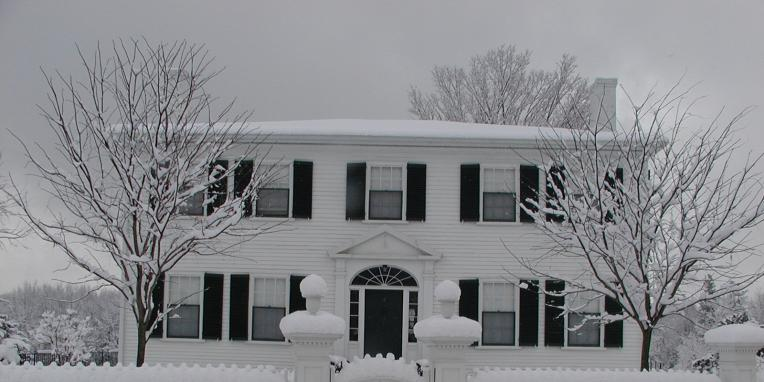 White house with black shutters in snow.